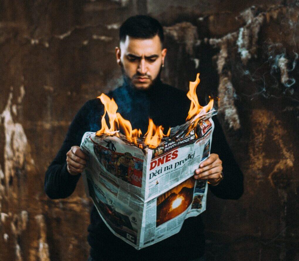 Man with burning newspaper