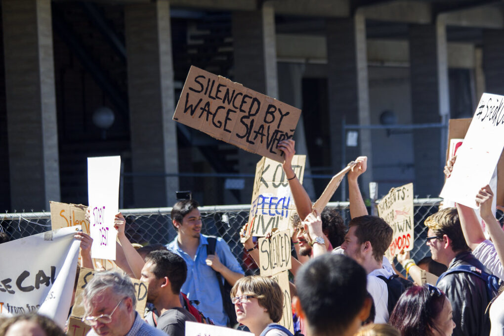 """Demonstrators holding sign saying """"Silenced by wage slavery'"""