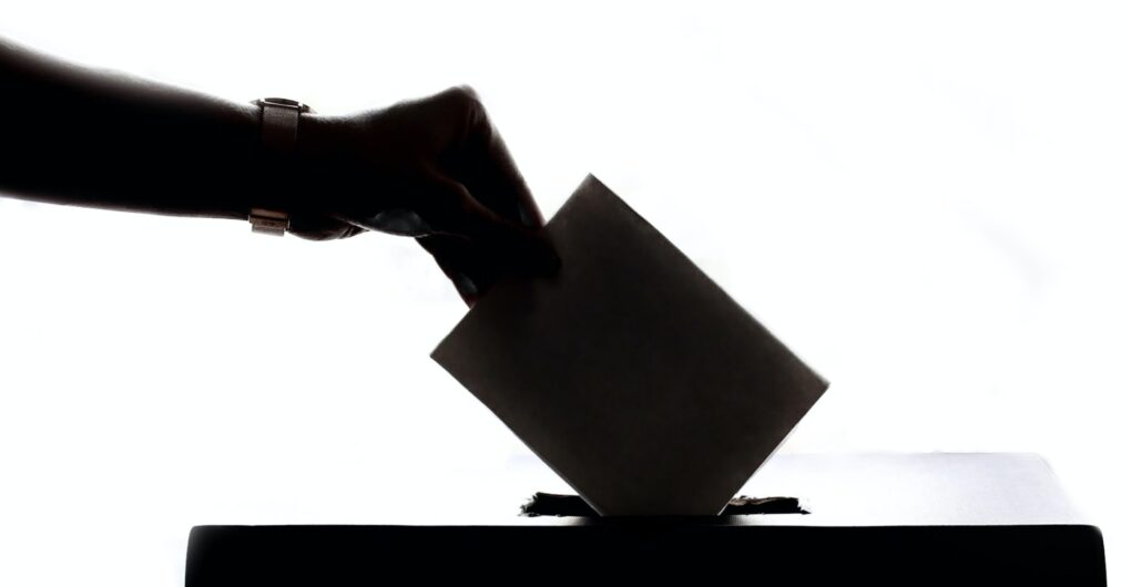 Vote being put in ballot box in shadow